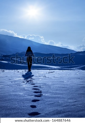 Image of lonely woman silhouette at winter mountains, footprints on the snow, enjoying wintertime nature view,one girl walking away on snowy path outdoor, winter cold weather, solitude concept - stock photo