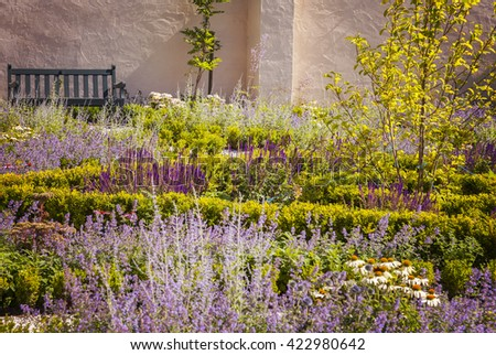 Image of lush landscaped walled garden.  - stock photo