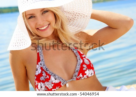 Image of luxurious woman in bikini and hat relaxing on the seashore - stock photo