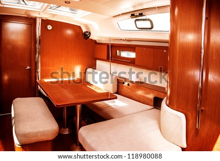 Image of luxury ship interior, comfortable sailboat cabin, expensive wooden design and soft white sofa inside on the yacht, holiday recreation, tourism, travel and vacation concept