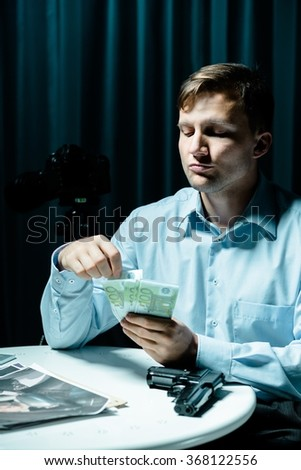 Image of madman counting money for murder - stock photo