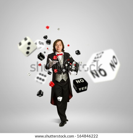 Image of magician in red bow-tie throwing dice - stock photo