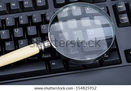 image of Magnifying glass on an black keyboard - stock photo