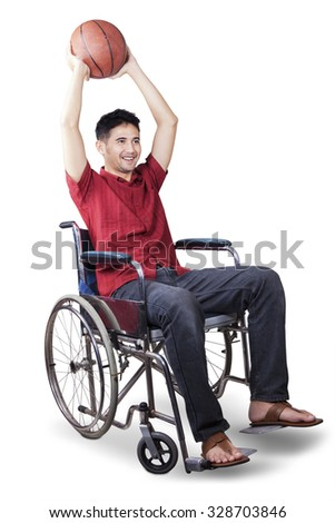 Image of male basketball player sitting on the wheelchair and ready to throw a ball, isolated on white - stock photo