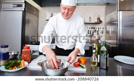 Image of male chef cooking meat in the kitchen - stock photo