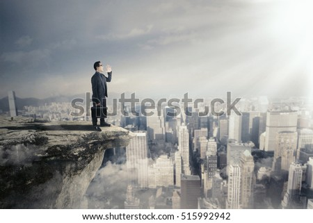 Image of male entrepreneur with a briefcase standing on the cliff while shouting by using a speaker