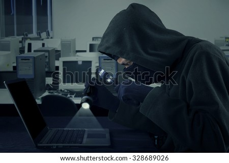 Image of male hacker stealing user identity on the laptop while wearing mask and using flashlight with magnifying glass - stock photo