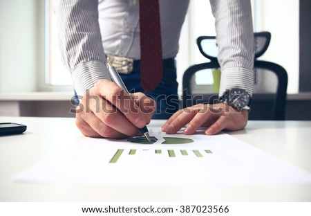 Image of male hand pointing at business document during discussion at meeting - stock photo