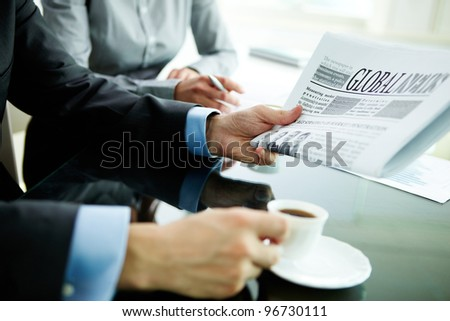 Image of male hand with newspaper and cup of coffee - stock photo