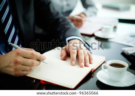 Image of male hand with pen over open notebook during planning work - stock photo