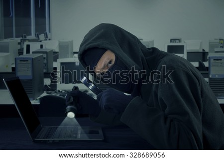 Image of male thief stealing user information on the laptop computer while wearing mask in the office - stock photo