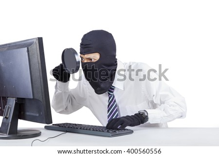 Image of male thief wearing mask and using magnifier to steal information on the computer, isolated on white background