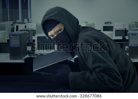 Image of male villain stealing laptop computer in the office while wearing mask and staring at the camera - stock photo