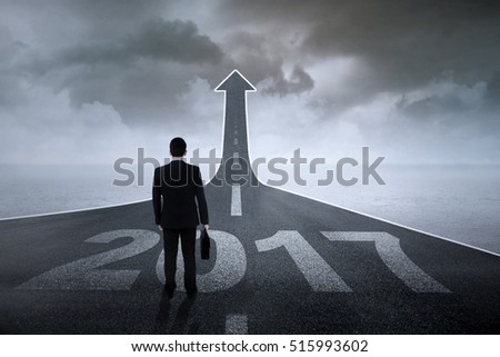 Image of male worker with a briefcase standing on a road with number 2017 and upward arrow