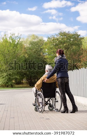 Image of man on wheelchair with private nurse outdoors - stock photo