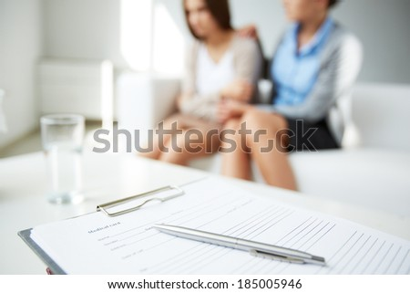 Image of medical card with pen on background of psychiatrist comforting her patient - stock photo