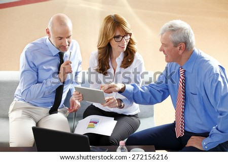 Image of middle age businesswoman holding digital tablet while sitting at office with businessmen and consulting from financial plan. Sales team at work. - stock photo