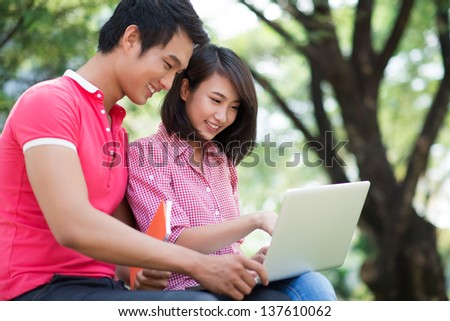 Image of modern students sitting with a laptop outside - stock photo