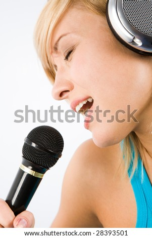 Image of modern teenage girl with headphones on head singing her favourite song into microphone