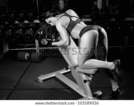 Image of muscle girl with dumbbells in gym - stock photo