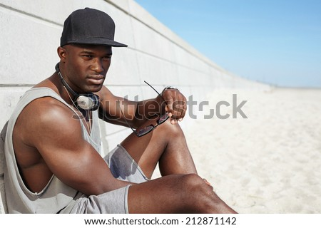 Image of muscular young african man sitting on a beach. Male model wearing a cap and headphones holding sunglasses looking away. - stock photo