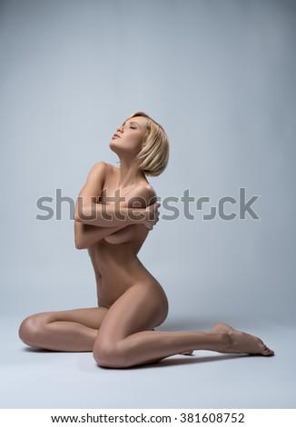 Image of naked blonde posing sensually at camera - stock photo