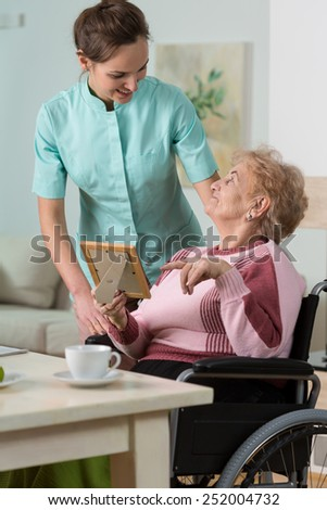 Image of nurse caring about handicapped woman - stock photo