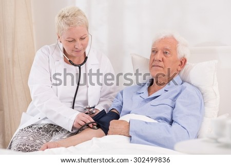 Image of nurse taking blood pressure of elderly man
