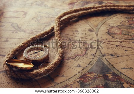 image of old compass and rope on vintage map