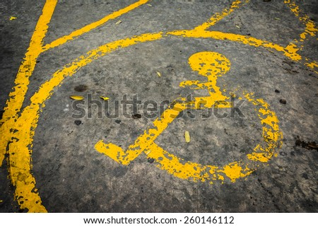 image of old Handicapped symbol on parking space. - stock photo