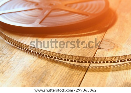 image of old 8 mm movie reel over wooden background. retro style image - stock photo