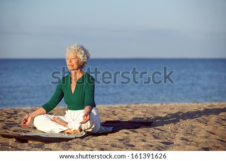 Image of old woman sitting on exercise mat practicing yoga on the beach. Senior caucasian woman meditating in lotus pose - Outdoors - stock photo