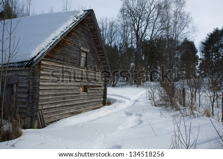 Image of old wooden house covered by snow - stock photo