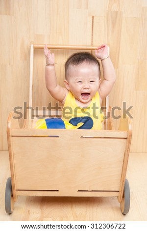 Image of one year old East Asian baby boy standing on wooden background, sweet little baby  smiling - stock photo