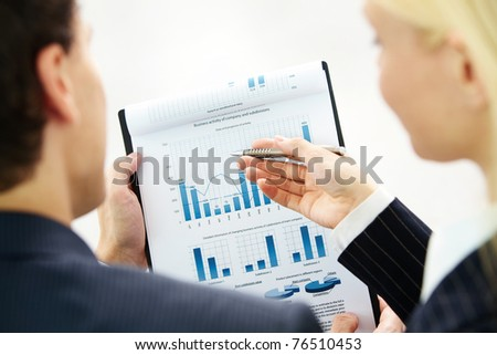 Image of paper being discussed by two business partners - stock photo