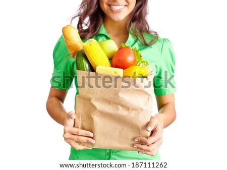 Image of paper packet full of different fruits and vegetables held by smiling female - stock photo