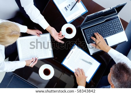 Image of partners hands during discussion of business plan at meeting - stock photo