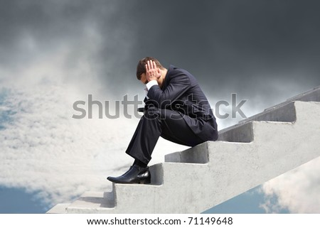 Image of pensive businessman sitting on stairs against thunderclouds - stock photo