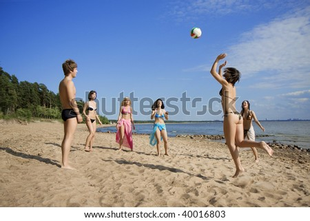 Image of people on the beach playing volleyball