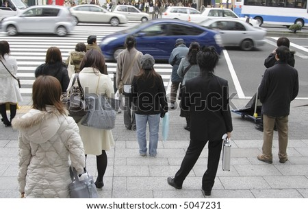Image of people waiting to cross the street in a big city. - stock photo