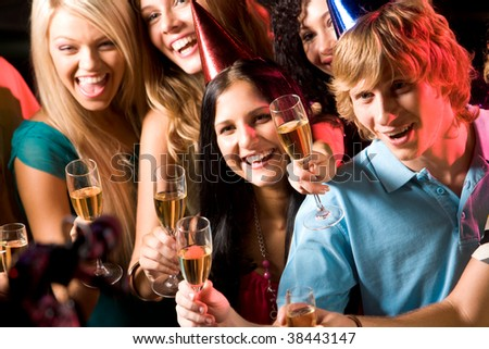 Image of people with hats holding glasses of champagne - stock photo