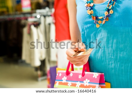 Image of personal credit card in female hand with shopping bags - stock photo