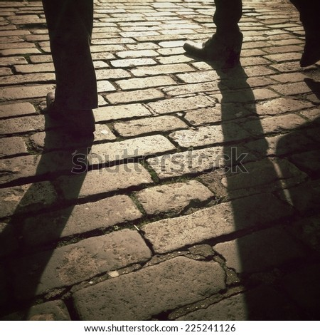 Image of persons walking over cobbled street in low bright sunlight, shot on a mobile phone with Instagram effect applied. - stock photo