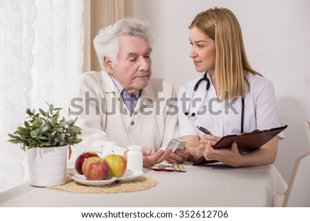 Image of physician writing healthcare program for old man - stock photo