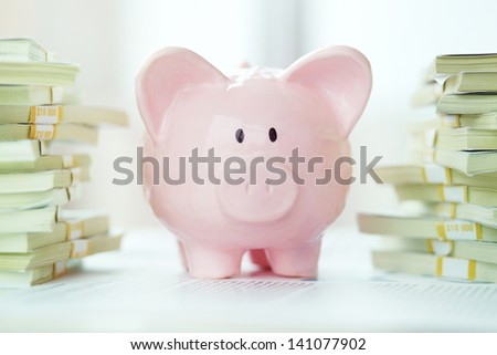 Image of pink piggy bank and stack of dollar bills - stock photo