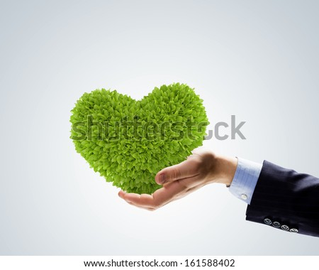 Image of plant in human hand shaped like heart - stock photo