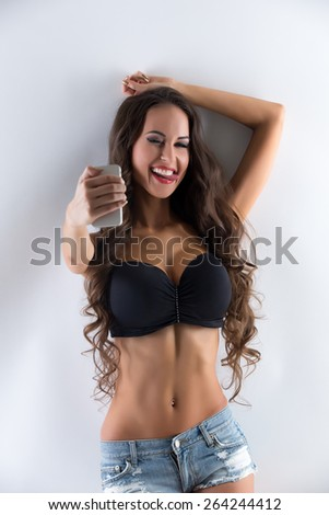 Image of playful busty woman doing selfie - stock photo