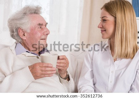 Image of positive private caregiver and content senior man - stock photo