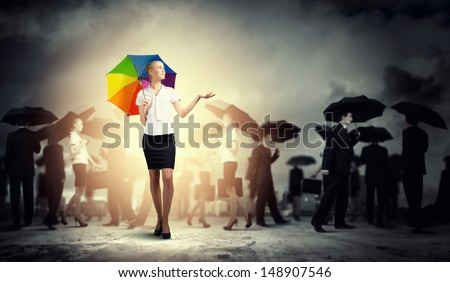 Image of pretty businesswoman with umbrella walking in crowd of people - stock photo