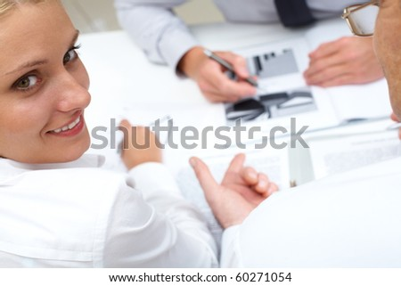 Image of pretty employee looking aside during conversation
